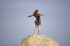 Feeling Powerful. A young woman stands on a rock with the wind in her hair feeling powerful