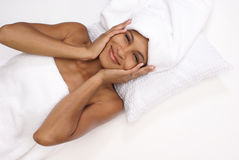 Feeling refreshed. Beautiful young woman lays down refreshed in her towels and feeling her soft skin Stock Images