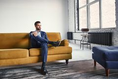 Feeling relaxed...Handsome and stylish young businessman is resting on sofa and thinking about business ideas. Fashion portrait. Business look royalty free stock photography