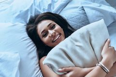 Feeling rested. Top view of attractive young woman embracing pillow and smiling while lying on the bed at home Stock Photo