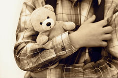 Feeling safe. Security concept. The boy is holding small teddy bear in his arms. In vintage style Royalty Free Stock Images