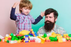 Feeling safe with dad. small boy with dad playing together. father and son play game. building home with colorful royalty free stock images