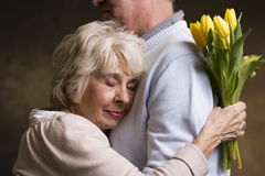 Feeling of safeness. An old women cuddling in strong arms of her beloved Stock Image