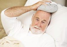 Feeling Sick. Senior man home sick with a cold, flu, or hangover Stock Photo