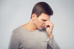 Feeling sick and tired. Frustrated young man massaging his nose, keeping eyes closed isolated on gray background. Royalty Free Stock Image