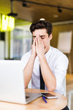 Feeling sick and tired, Frustrated young man massaging his nose and keeping eyes closed while sitting at his working place in offi. Frustrated young man royalty free stock images