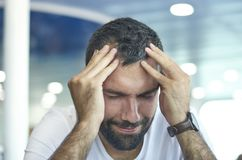 Feeling stressed. Frustrated handsome young man touching his head and keeping eyes closed while sitting on a chair, blur. Background adult beard beauty royalty free stock images
