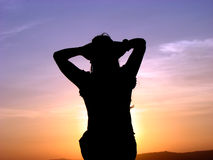 Feeling the Sun. A woman relaxing and feeling the warmth of the setting sun Royalty Free Stock Photos
