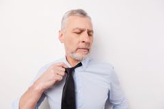 Feeling so tired. Tired senior man in shirt taking off his necktie while standing against white background Royalty Free Stock Photos