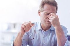 Unhappy moody man holding the bridge of nose. Feeling of tiredness. Unhappy moody adult man sitting at the table and holding the bridge of his nose while taking Stock Photo