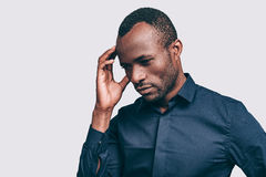 Feeling uncertain. Handsome young African man touching head with hand and looking uncertain while standing against grey background stock photos