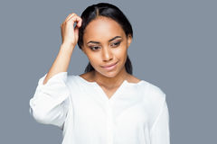 Feeling uncertain. Thoughtful young African woman holding hand in hair and looking away while standing against grey background Royalty Free Stock Photography