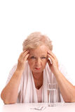 Feeling unwell. Portrait of sick aged woman touching head with tablets near by Stock Photo