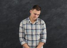 Feeling upset, sad man portrait. Feeling upset. Portrait of young sad man. Young unhappy guy grimacing, gray studio background Stock Photos