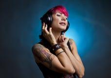 Feeling the vibe. Tattooed girl listening music on headphones and feeling the vibe Stock Image