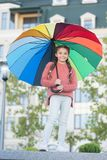 Feeling warm. Optimist and cheerful child. Spring warm. Positive mood in autumn warm weather. Multicolored umbrella for. Little happy girl. Little girl under stock photography