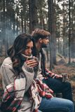 Feeling the warmness. Young beautiful couple enjoying hot drinks. While sitting in the forest Royalty Free Stock Photo