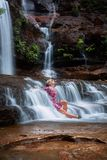Exhilaration in mountain waterfall, female sitting in flowing cascades. That feeling of the water rushing past as you sit in its rapid flows as it motions past stock photos