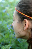 Feeling the wildflowers. Young woman smelling the aroma of bluebells Stock Images