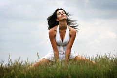 Feeling the wind. Attractive young woman sitting on grass feeling the wind on her face Royalty Free Stock Photography