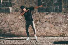 Feeling young and carefree. Full length of handsome young African man in casual clothes moving and gesturing while standing against the stoned wall outdoors Stock Photo