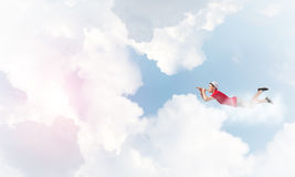 Feeling young and free. Young cheerful man flying high in sky and playing fife Royalty Free Stock Photos