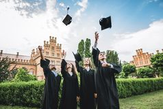 It feels amazing to finally graduate!Four happy college graduates in graduation gowns throwing their mortar boards and smiling. While standing near university stock image
