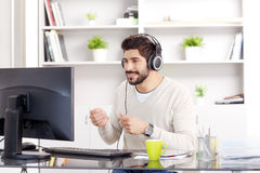 Feels the beat. Portrait of young businessman sitting at his working place in front of his computer. Professional man with headphone feels the beat while Royalty Free Stock Photo