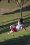 Feels Good. Little girl resting on slope enjoying warm sun & a soft breeze Stock Photos