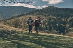 Feels like flying. Full length of happy young couple smiling while running on the valley in mountains outdoors Stock Images