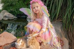 Feemeisje met konijnen in tuin Stock Fotografie