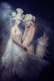 Feenhafte Kunstbilder der Engelsnymphe von Frauen Mädchen mit Engel beflügelt, die Schönheitsmodelle, die auf einem dunklen Hinte Stockfotos