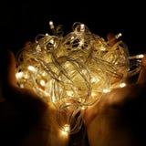Feenhafte Lichter auf Händen Stockbilder
