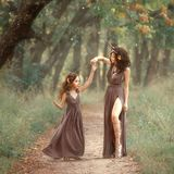 Feenhafte Mutterrotwild auf dem Weg, der ihre Tochter auf einer Schneise, tragende lange braune Kleider, ihr reizend Bein zeigend stockfotografie
