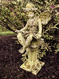 Feenhafte Statue auf Säule im Garten Stockbild