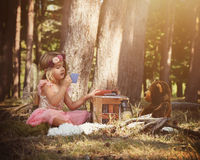 Feenhaftes Mädchen, das mit Teddy Bear im Holz spielt stockfoto