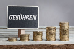 Fees in German language on sign. Gebühren tariffs in German language, white chalk type on black board, Euro money coin stacks of growth on wood table royalty free stock photo