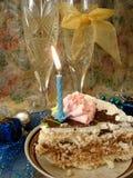 Feest lijst (stuk van verjaardagscake en blauwe kaars, twee g Royalty-vrije Stock Afbeelding