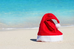 Feest Rode Santa Claus-hoed op strandachtergrond Stock Foto