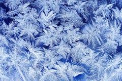 feestelijk ijzig patroon met witte sneeuwvlokken op een blauwe achtergrond op glas Stock Fotografie