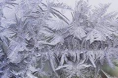 Feestelijk ijzig patroon met witte sneeuwvlokken op glas Stock Foto