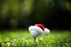 Feestelijk-kijkend golfbal op T-stuk met de hoed van de Kerstman stock foto's