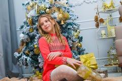 Feestelijk meisje die een gift thuis openen Stock Foto