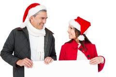 Feestelijk paar die met santahoed een witte affiche houden Stock Afbeelding