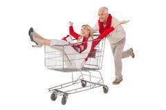 Feestelijk paar die ongeveer in het winkelen karretje knoeien Royalty-vrije Stock Foto's