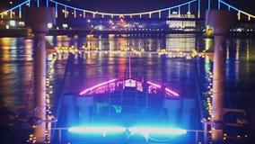 Feestelijk schip die de heldere brug naderen die bij nacht gloeien stock videobeelden