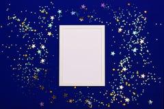 Feestelijke achtergrond met leeg wit fotokader op donkerblauw met confettien stock afbeeldingen