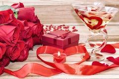 Feestelijke achtergrond van de dag van Valentine Een boeket van rode rozen, een giftdoos, een hart-vormige kaars en een rood lint stock foto's