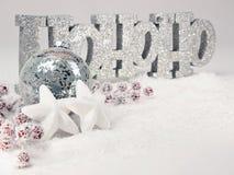 Feestelijke decoratie met HoHoHo-bericht, zilveren snuisterij en witte sterren in de sneeuw Stock Fotografie
