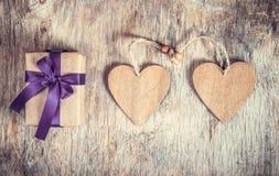 Feestelijke decoratie voor de Dag van Valentine ` s Twee houten harten en een giftdoos met een boog op een houten achtergrond Royalty-vrije Stock Foto